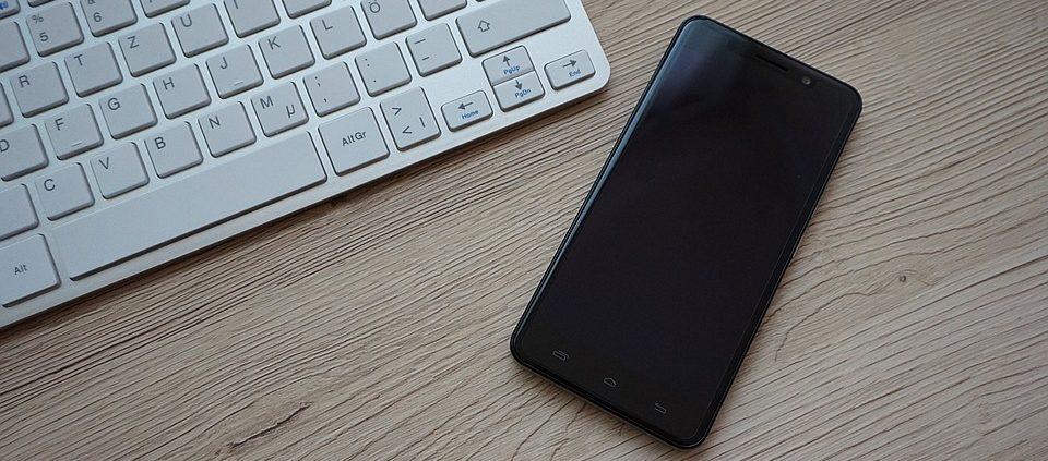 Ein Smartphone und ein Laptop liegen auf dem Tisch.