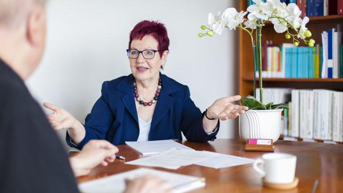 Die Anwältin sitzt am Besprechungstisch. Darauf liegen Unterlagen. Sie berät einen Mandanten, der nur von hinten zu sehnen ist.