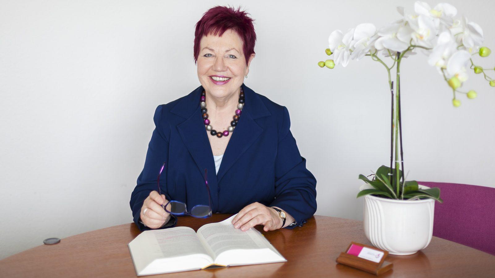 Rechtsanwältin Karin Schwarz-Feuring sitzt am Besprechungstisch und hält eine Brille in der Hand. Auf dem Tisch liegt ein Gesetzestext, eine weisse Orchidee und Visitenkarten.