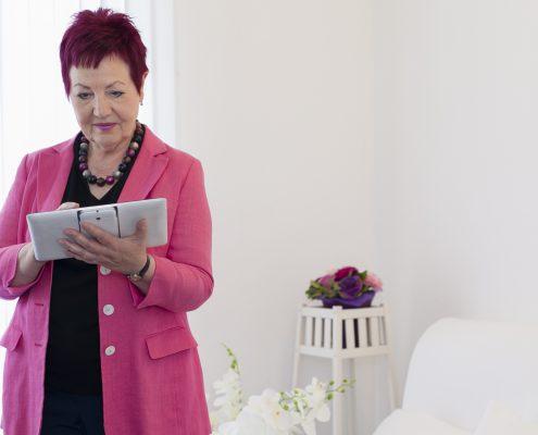 Rechtsanwältin Karin Schwarz-Feuring steht im Büro und arbeitet mit einem Tablet. Im Hintergrund sieht man Blumen.
