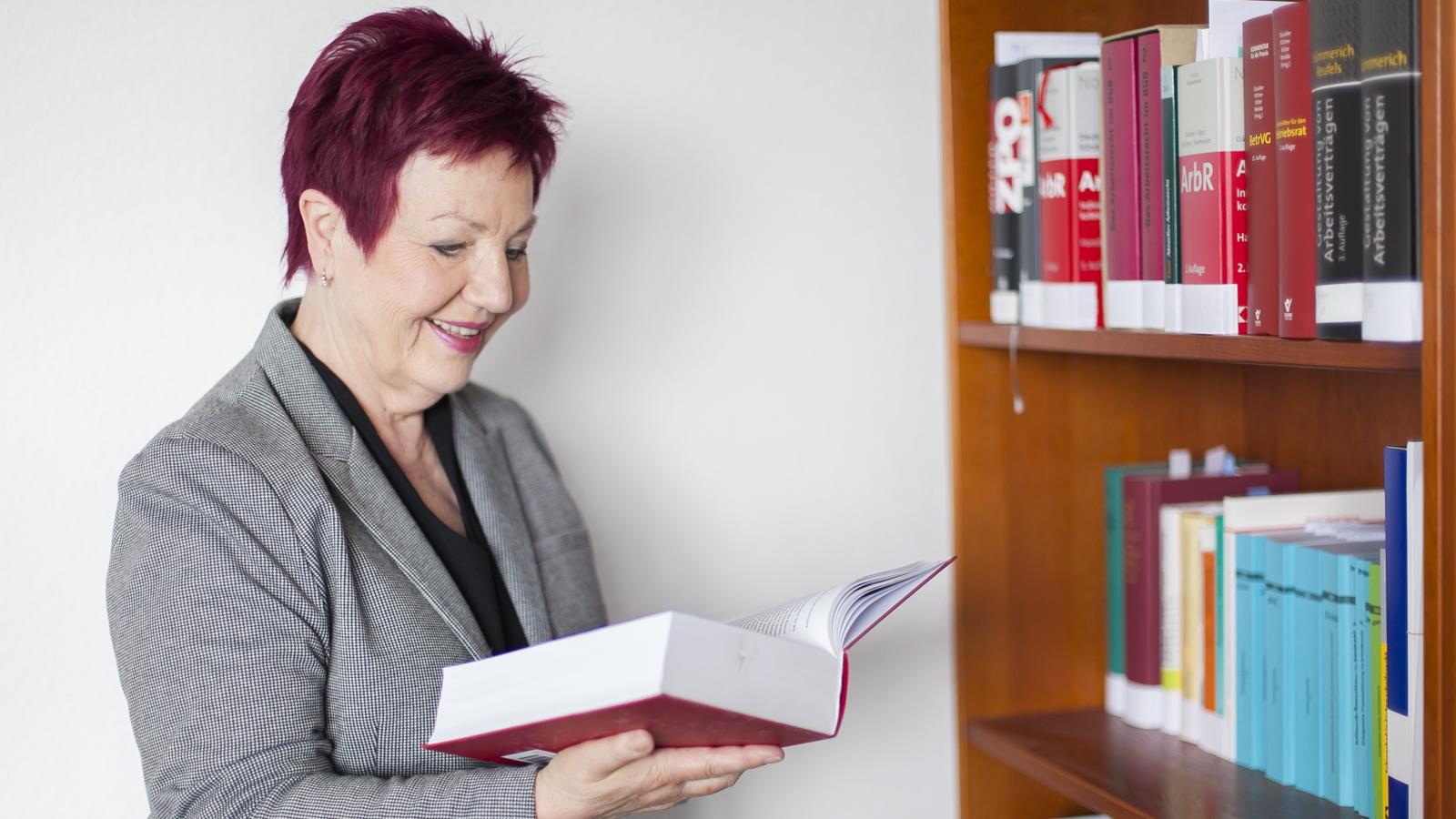 Die Anwältin hält ein Buch in der Hand, liest und steht vor eine Bücherregal.
