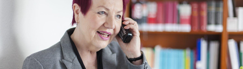 Frau Schwarz-Feuring telefoniert. Im Hintergrund steht ein Bücherregal.