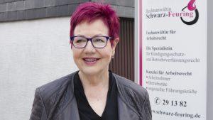 Frau Schwarz-Feuring steht vor Ihrem Kanzleischild.